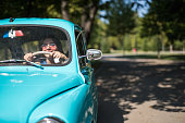 istock Young woman driving vintage car 1216181836