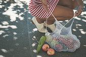 若い女性が歩道に食料品をドロップ