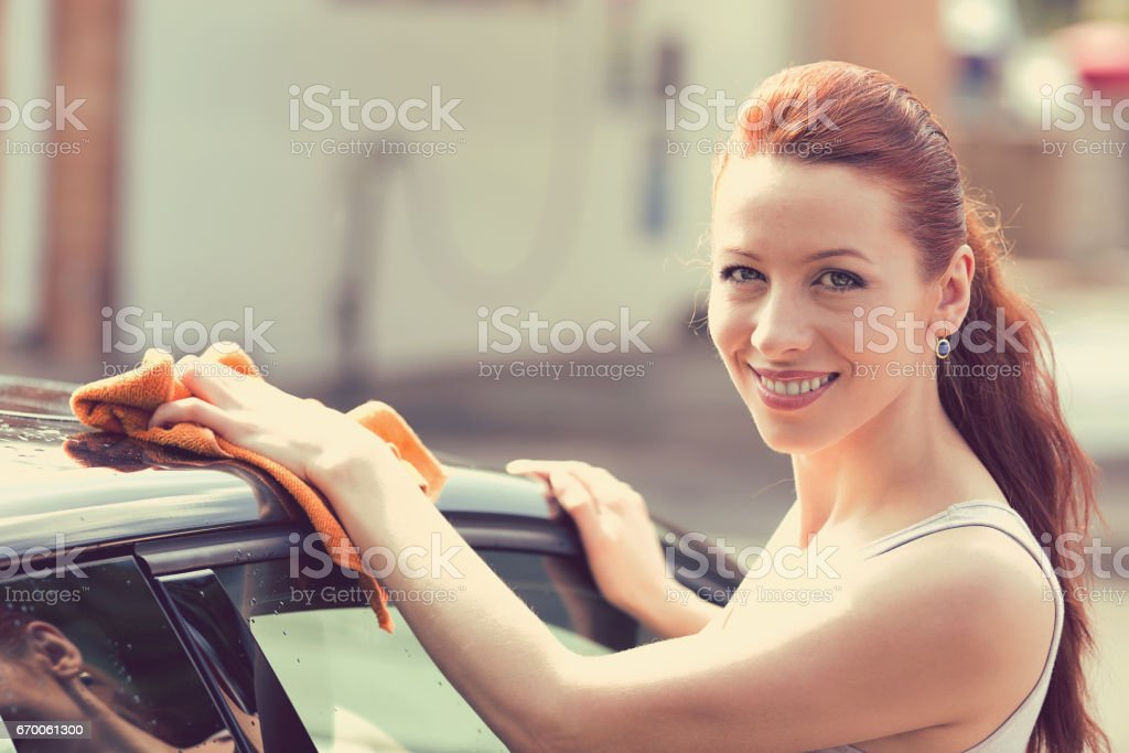 Young woman dry wiping her car with microfiber cloth after washing it, cleaning auto stock photo