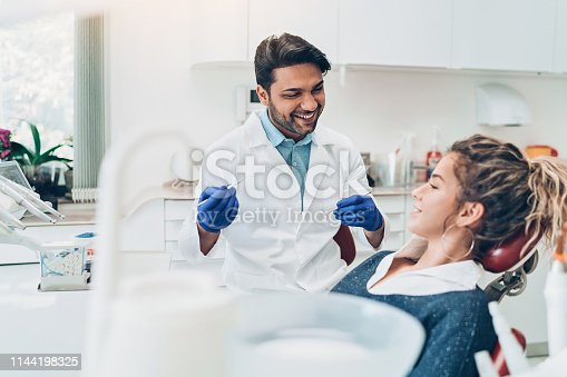 istock Young woman during a dental check-up 1144198325