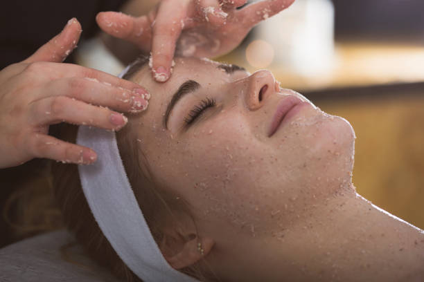 Young woman during face salt scrub therapy stock photo