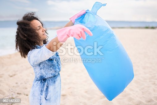 962184460 istock photo Young woman during local clean up at the beach 962182302