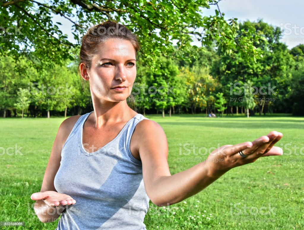 Young woman during tai chi exercise in the park stock photo