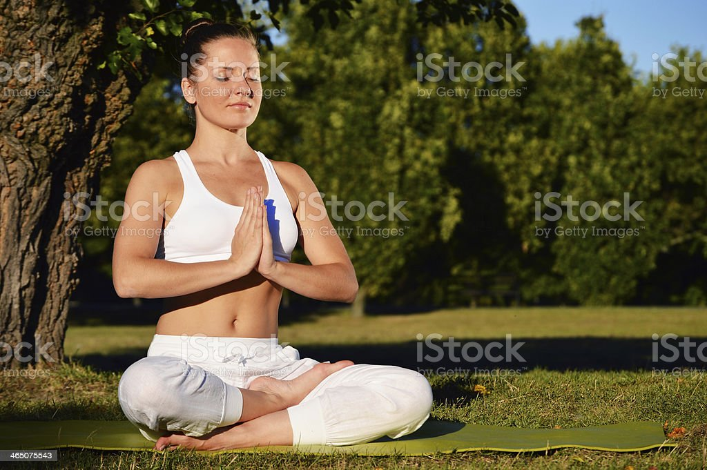 Young woman during yoga meditation in the park royalty-free stock photo