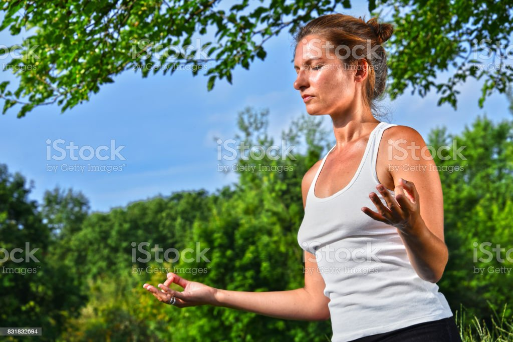 Young woman during yoga meditation in the park stock photo