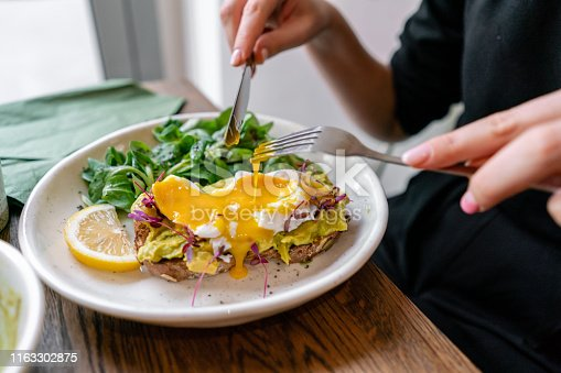 Young woman eat breakfast with knife and fork, Morning in cafe. Healthy breakfast with wholemeal bread toast with avocado, poached egg with green salad.