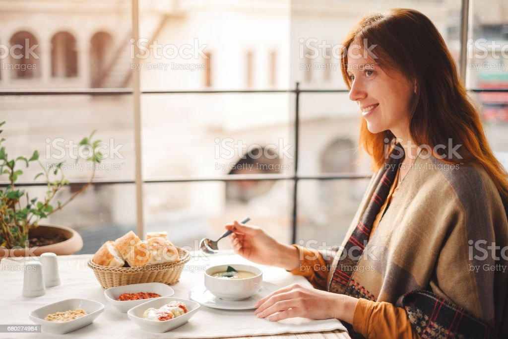 Young woman eat traditional turkish food from lentil soup stock photo