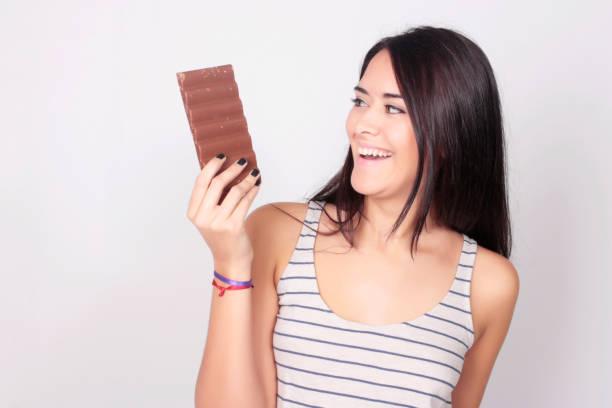 jovem mulher comer uma barra de chocolate - belas mulheres argentina - fotografias e filmes do acervo