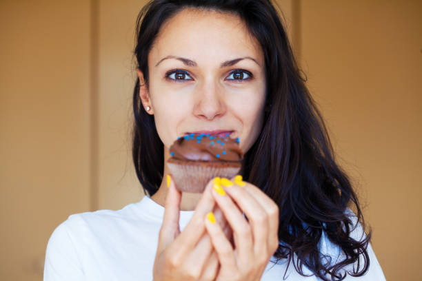 Young woman eating a cupcake stock photo