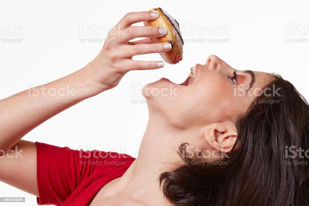 jonge vrouw die het eten van een donut - Royalty-free 20-29 jaar Stockfoto