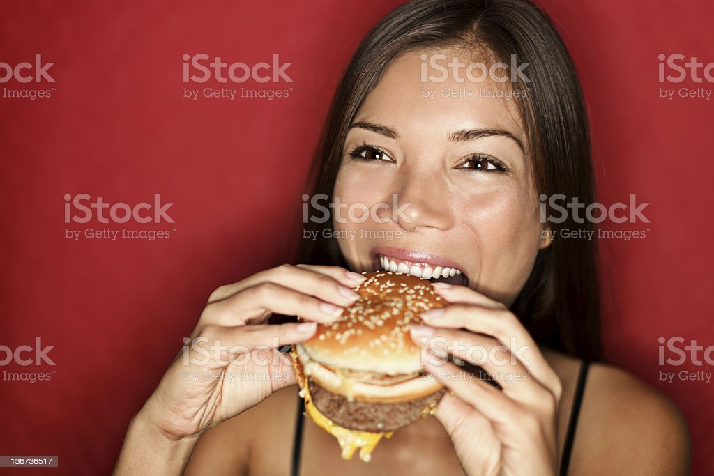 A young woman eating a hamburger stock photo