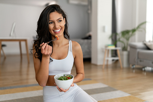 Young fit woman eating healthy salad after workout. Fitness and healthy lifestyle concept.