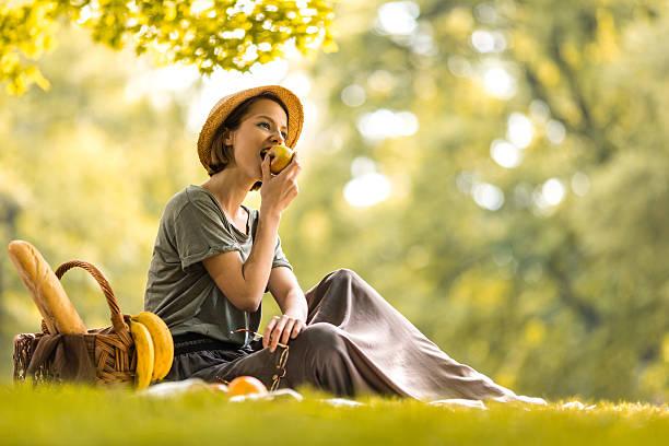 junge frau isst einen apfel auf picknick im frühling. - mensch isst gras stock-fotos und bilder