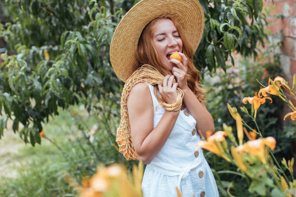 Young  woman eating apricot  in garden stock photo