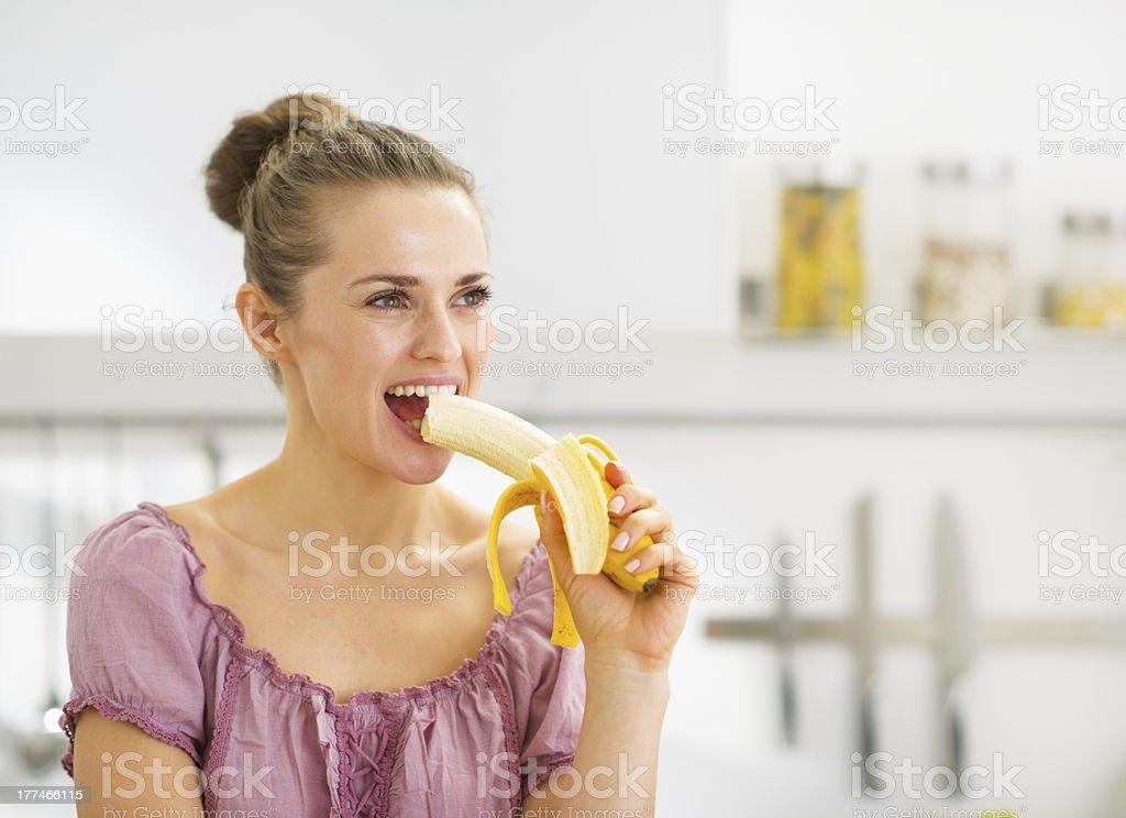 Junge Frau Essen Banane in der Küche – Foto
