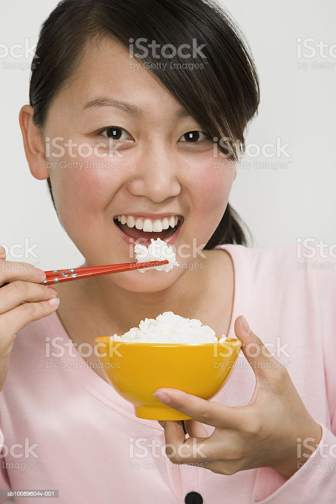 Young woman eating bowl of rice with chopsticks, portrait royalty-free stock photo