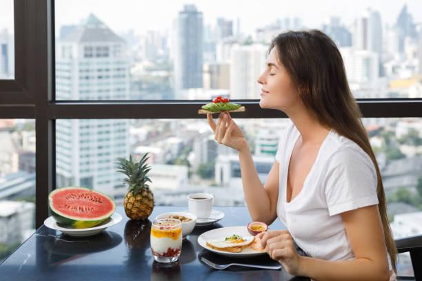 jeune femme avoir déjeuné au matin - infusion pamplemousse photos et images de collection