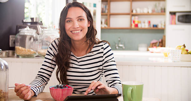 Young Woman Eating Breakfast Whilst Using Digital Tablet Young Woman Eating Breakfast Whilst Using Digital Tablet medium shot stock pictures, royalty-free photos & images