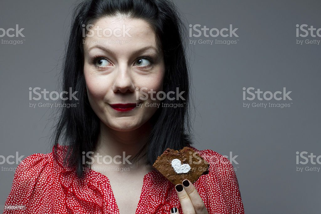 Young woman eating brownie Portrait of young woman eating brownie. Adult Stock Photo