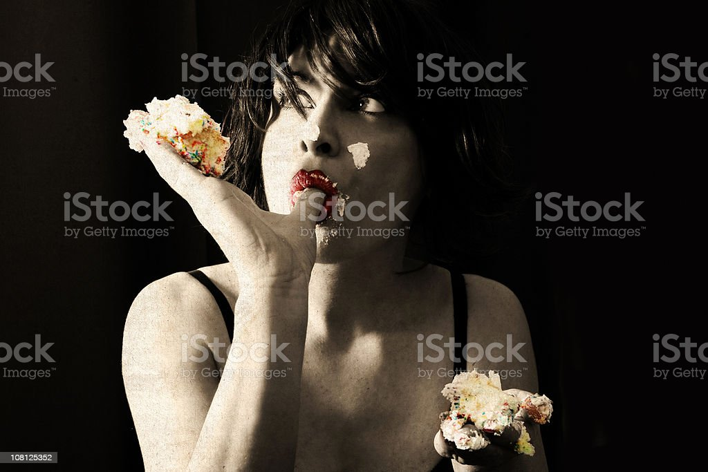 Young Woman Eating Cake with Hands stock photo