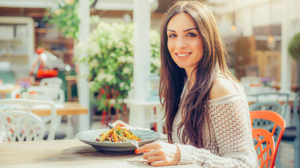 Young woman eating chinese food in a restaurant, having her lunch break stock photo