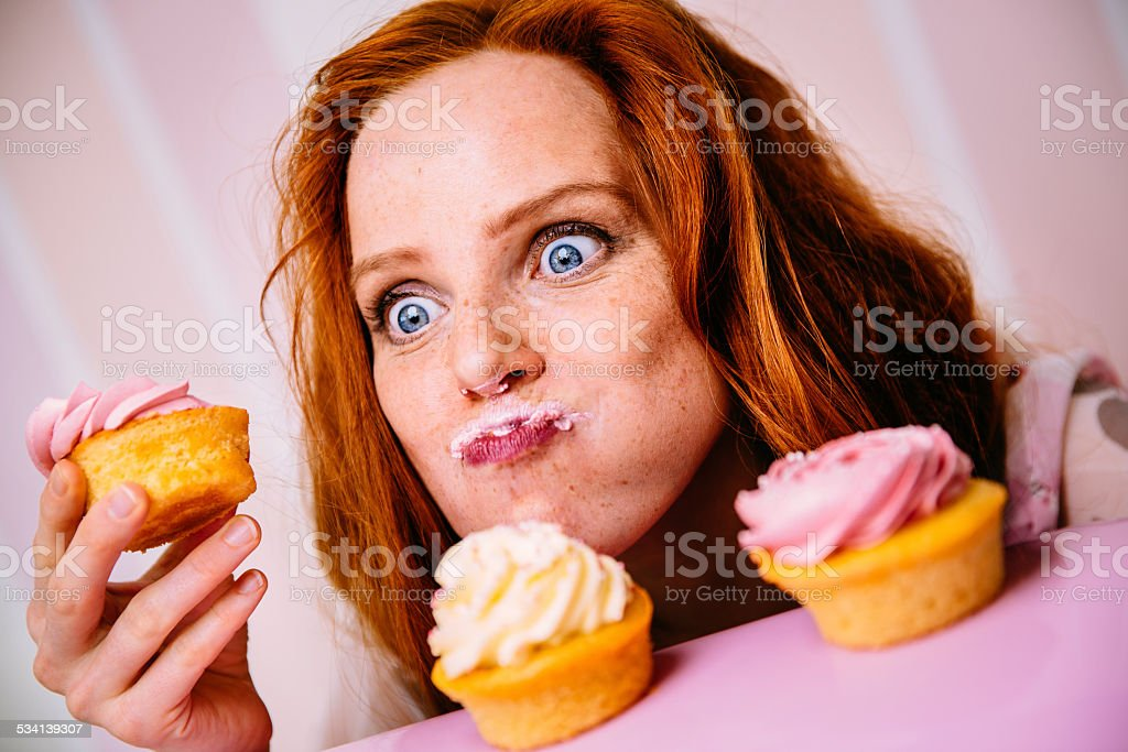 Young Woman Eating Cupcakes With A Lot Of Enthusiasm stock photo