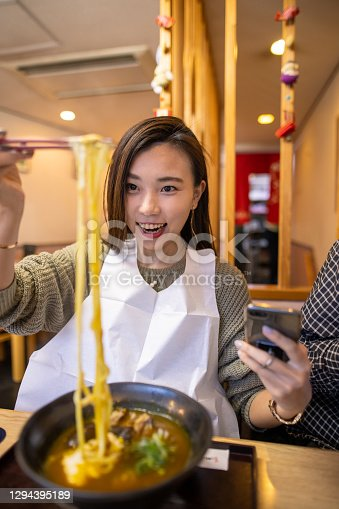 istock Young woman eating curry udon noddle for lunch 1294395189