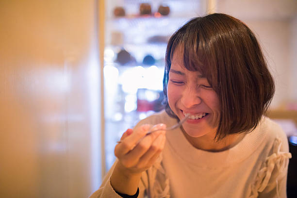 Young woman eating dessert with smile ストックフォト