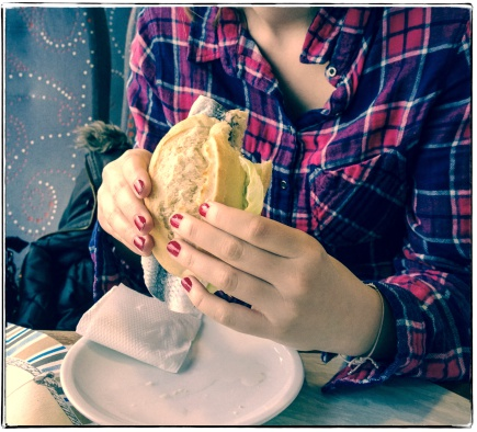young woman eating fish sandwich, retro style
