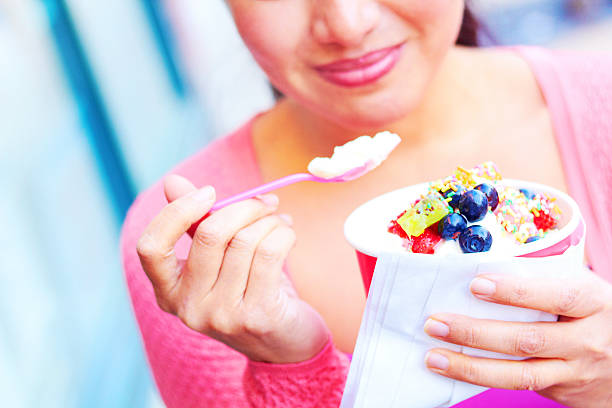 young woman eating frozen yogurt topped with assorted sweets - 冷凍乳酪 個照片及圖片檔