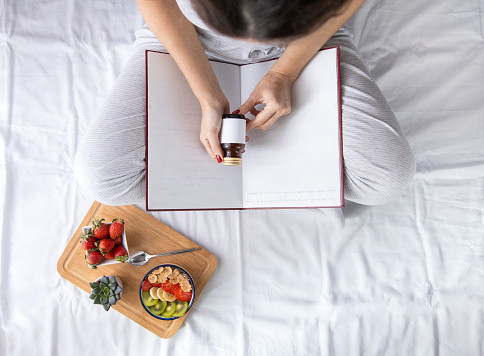 683349444 istock photo Young woman eating healthy breakfast in bed 1203565185