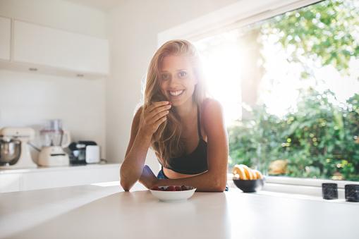 istock Young woman eating healthy breakfast 629960504
