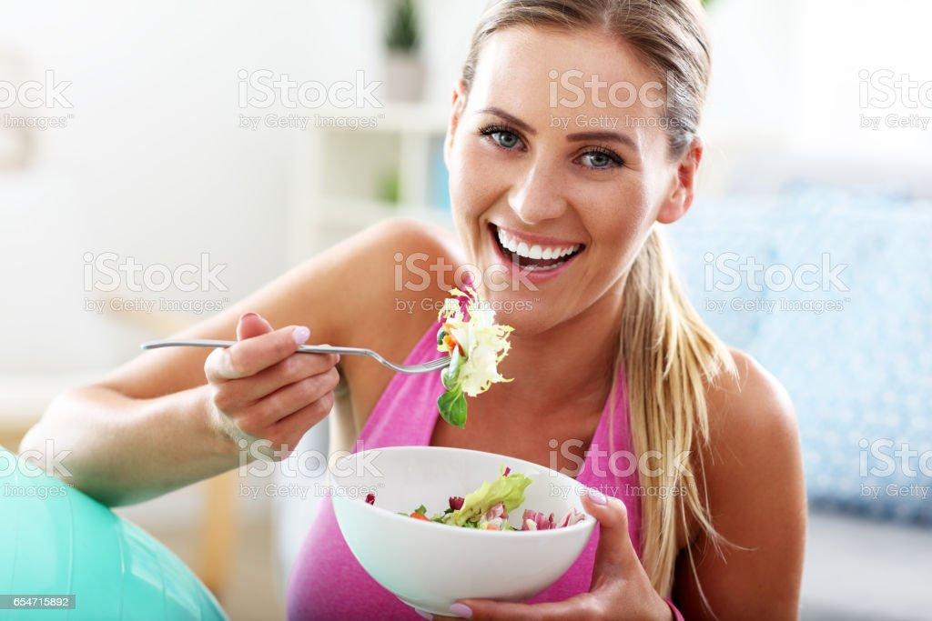 Mujer joven comer ensalada saludable después de entrenamiento - foto de stock
