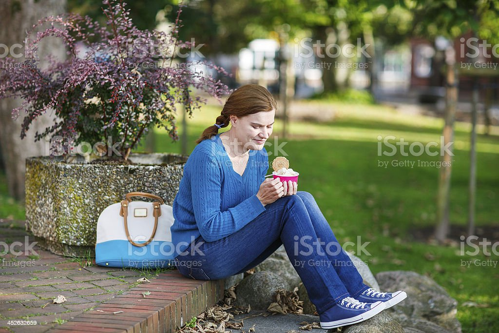Young woman eating ice cream in summer park. royalty-free stock photo