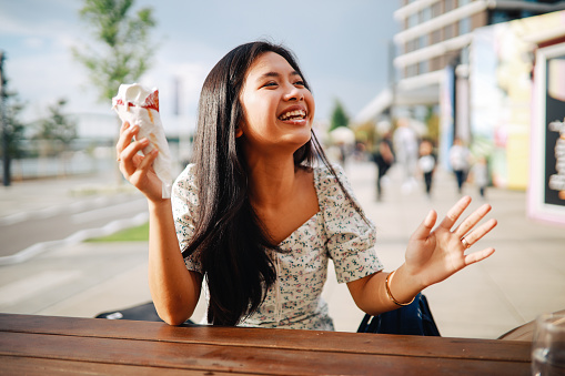 Young woman sitting in the outdoors café and eating ice cream.