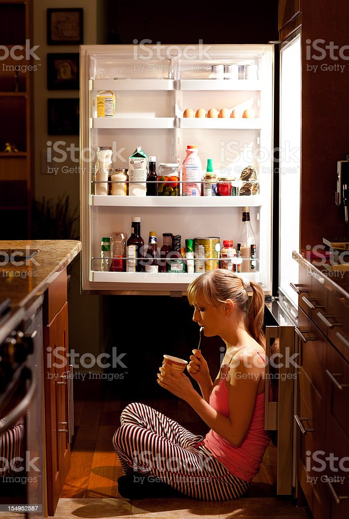 Young woman eating near refrigerator at night stock photo