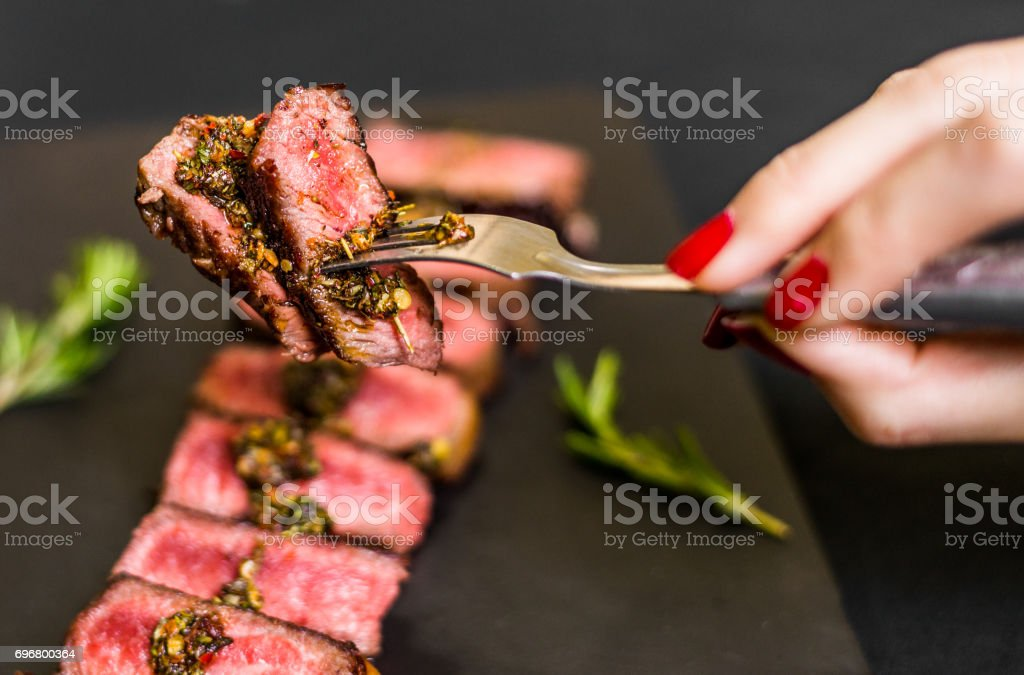 Young woman eating new york strip porterhouse steak meat stock photo