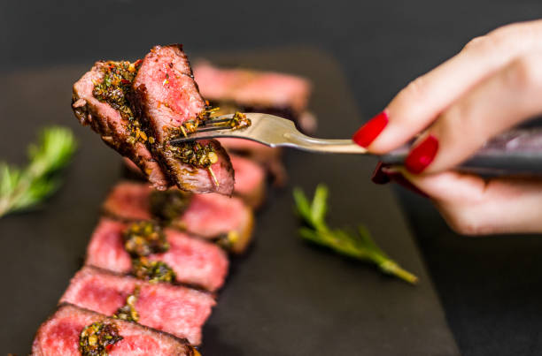 Young woman eating new york strip porterhouse steak meat Hands of a woman eating medium rare steak red meat stock pictures, royalty-free photos & images