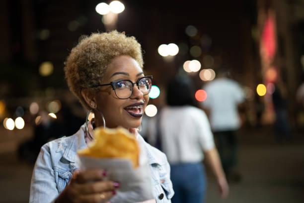 jovem mulher comendo pastel na rua depois do trabalho - pastel de feira - fotografias e filmes do acervo