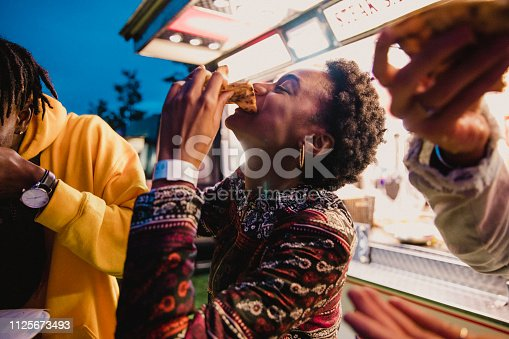 A young women enjoying pizza with friends at a music festival.
