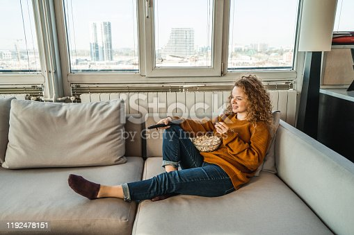 Young woman eating popcorn and watching movie