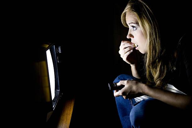 junge frau essen popcorn vor dem fernseher - serien schauen stock-fotos und bilder