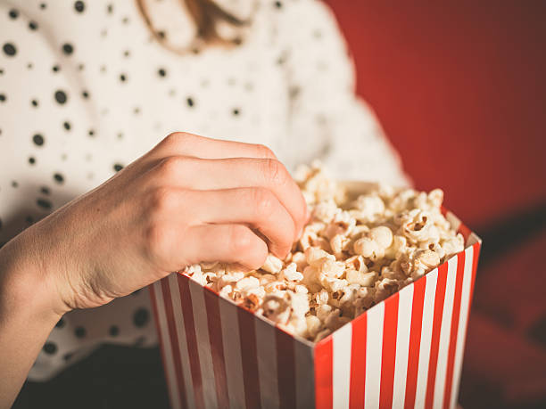 Young Woman Eating Popcorn in Movie Theater stock photo