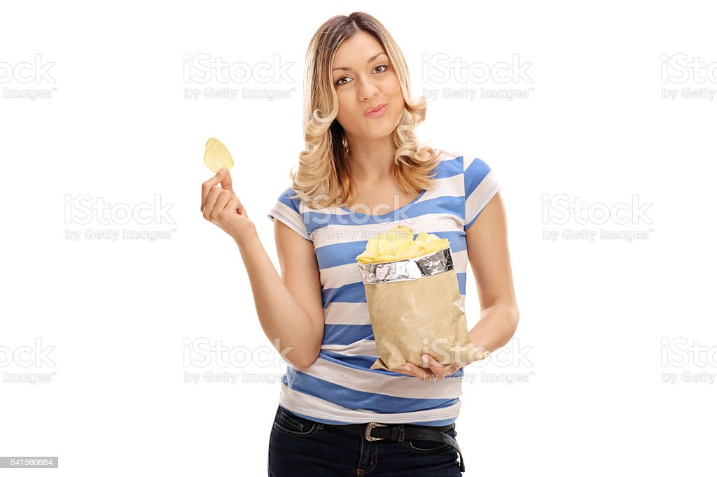 Young woman eating potato chips stock photo
