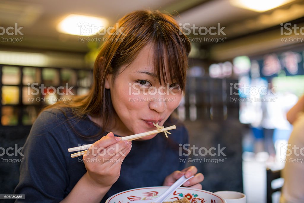 Young woman eating ramen noodle in old Japanese restaurant stock photo