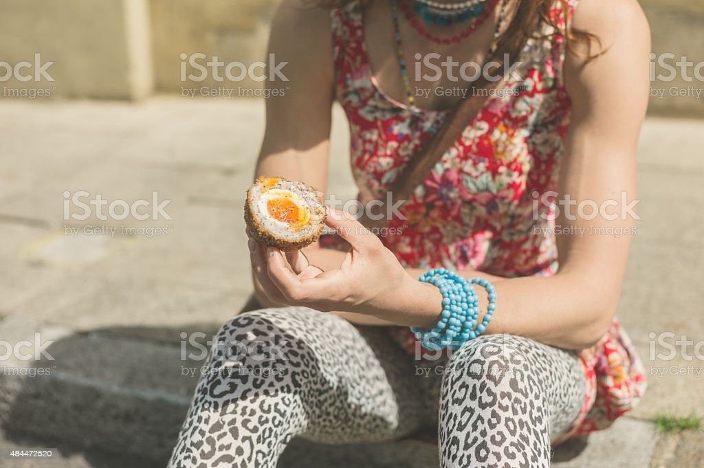 Young woman eating scotch egg in the street stock photo