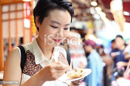 A young woman exploring a fish market and trying seafood delicacies.