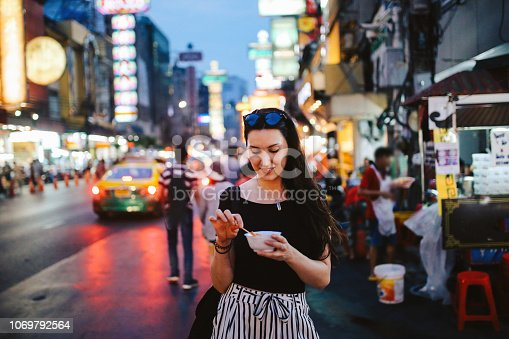 Portrait of a young brunette woman, walking on the streets of Bangkok Chinatown district. She is wearing casual street style clothing, trying out Thai food on the go. Delicious deep fried shrimp tempura dipped in hot sauce.