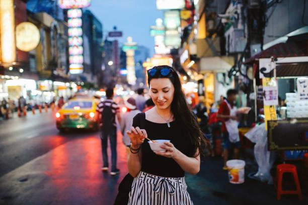 jonge vrouw eten garnaal tempura bangkok chinatown district, thailand - thai food stockfoto's en -beelden