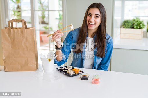 Young woman eating sushi asian food and noodles using choopsticks from take away delivery